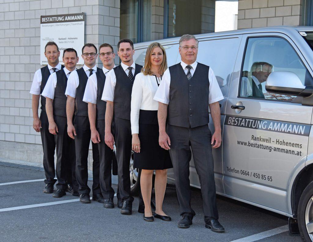 sechs Männer und eine Frau vor einem silbenen Lieferwagen